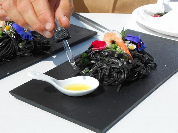 Tagliolini al nero di seppia con mazzancolle piselli e olio essenziale al basilico